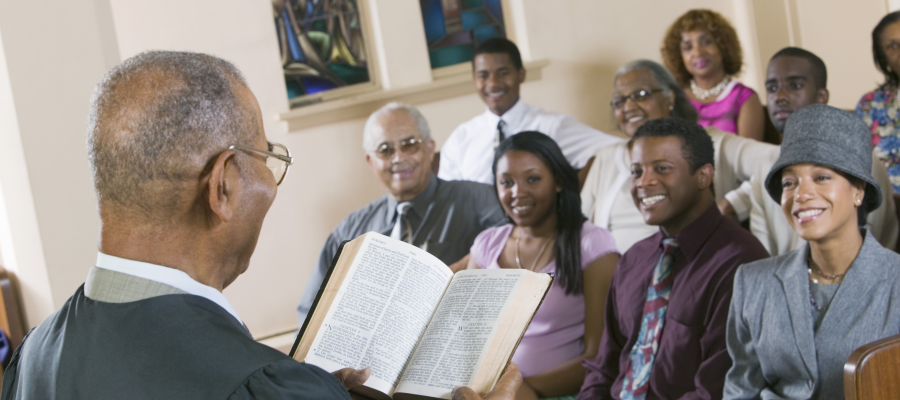Man reading a bible to the congregation explaining Church Giving and The Truth About Tithing