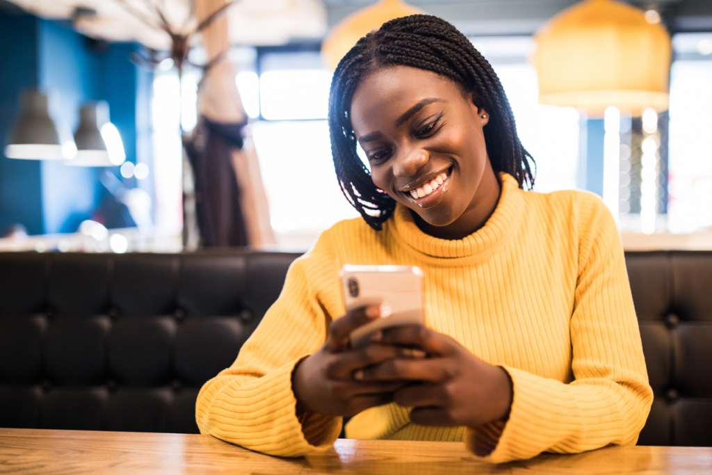 Young African American woman in a yellow turtleneck sits at a table, smiling and holding her smart phone after downloading the Givelify app for mobile and online giving.