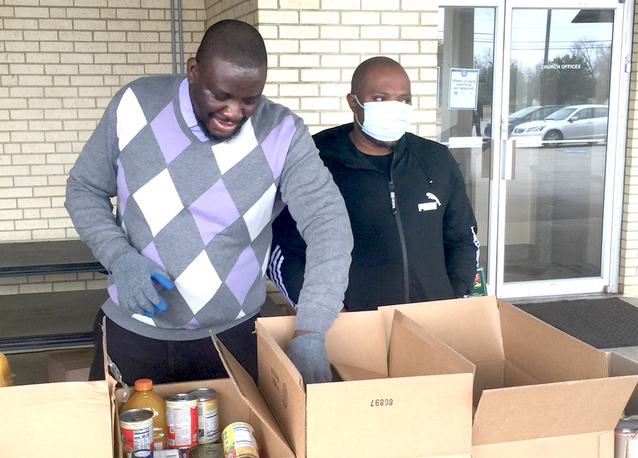 Yemi Salud volunteers at his church's food drive, packing food into boxes to hand out to families.