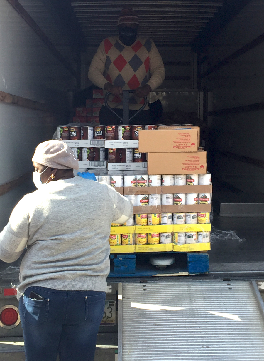 Volunteers unload pallets of food from a moving truck for their church food drive through.