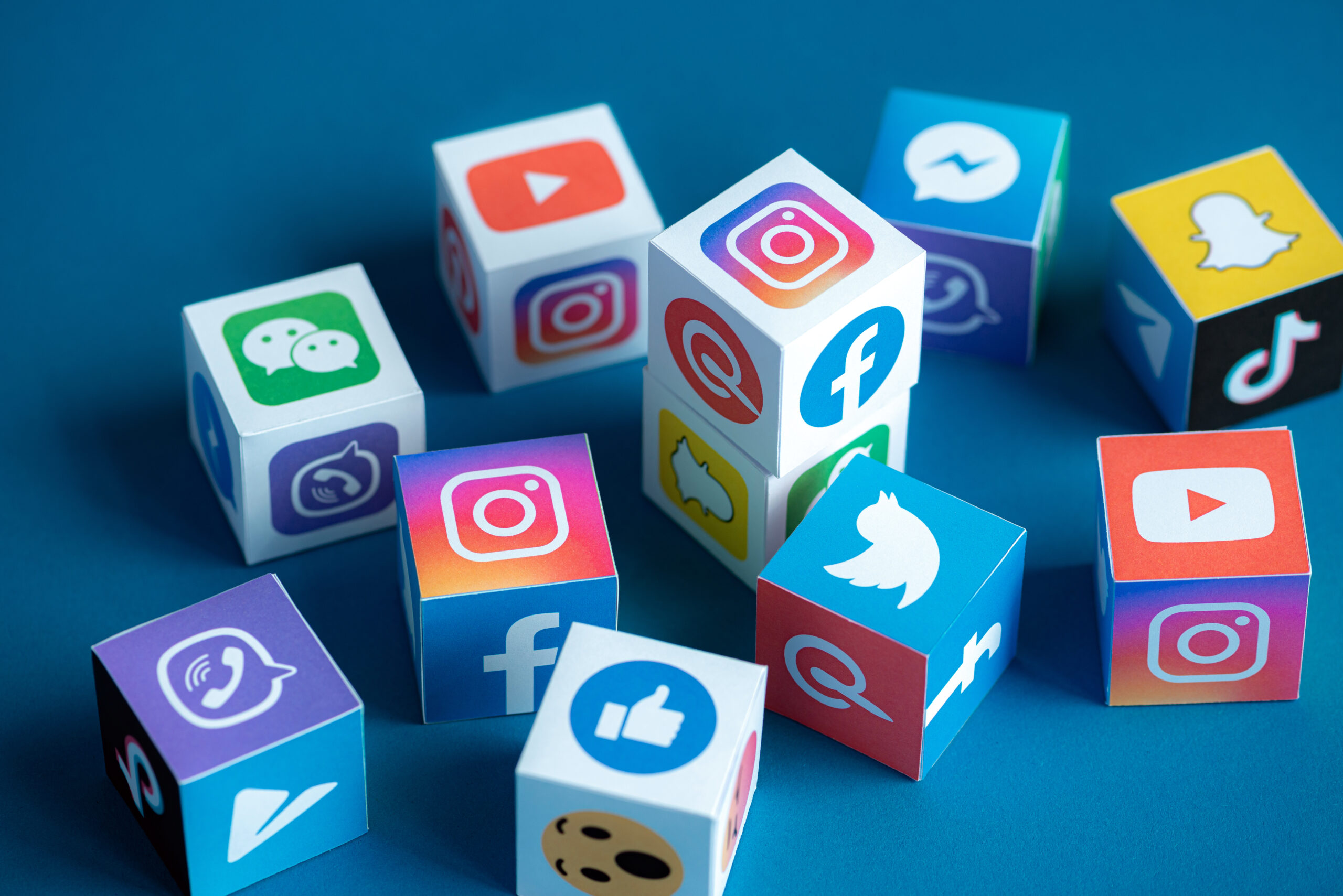 icons of popular social media apps appearing on a bunch of cubes, scattered on a table like dice