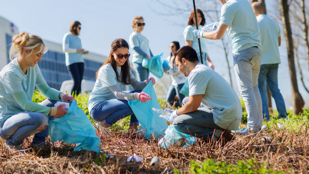 A group of happy non profit volunteers cleaning up some roadside litter