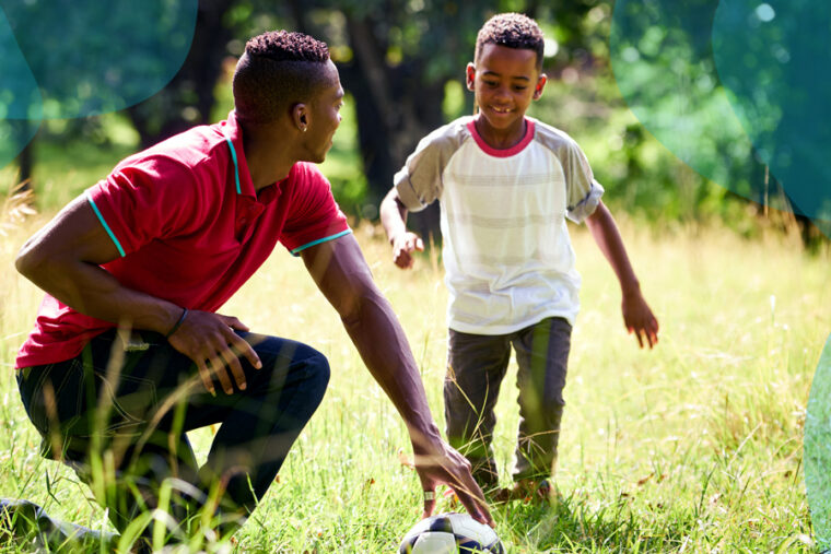 A father and a son in field playing together.