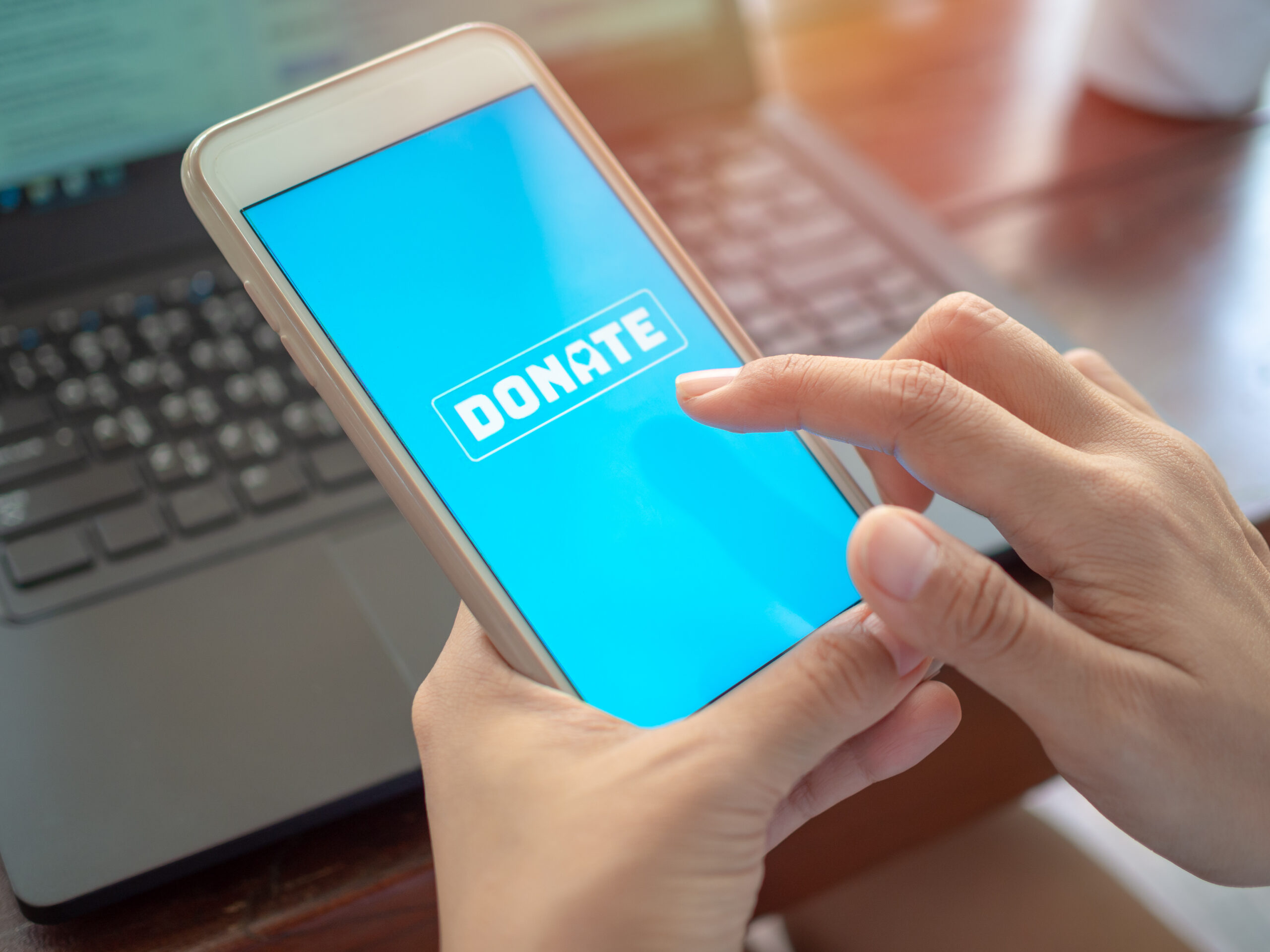 hands holding a mobile phone about to donate online