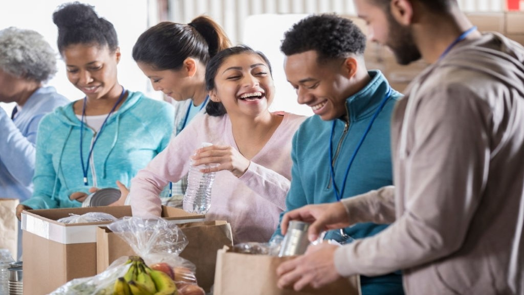 volunteers laughing while packing food for a charity