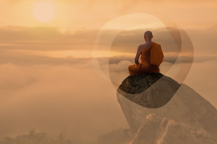 Buddist monk on a rock outcropping, meditating